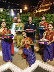 Stephen Cervantes in Thailand holding a cake, surrounded by costumed Thai people